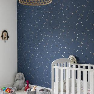 Ispirazione per una grande cameretta per neonata minimal con pareti blu, moquette e pavimento grigio