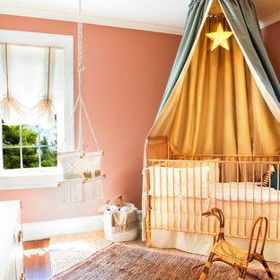 Cette image montre une chambre de bébé fille bohème de taille moyenne avec un mur rose, moquette et un sol beige.