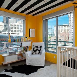 Exemple d'une chambre de bébé neutre tendance avec un mur orange et béton au sol.