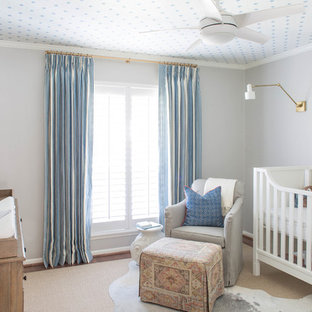 This is an example of a medium sized beach style nursery for boys in Houston with grey walls and dark hardwood flooring.