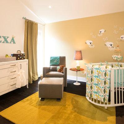 Example of a trendy gender-neutral dark wood floor nursery design in Vancouver with beige walls