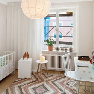 Idéer för mellanstora nordiska könsneutrala babyrum, med grå väggar och ljust trägolv