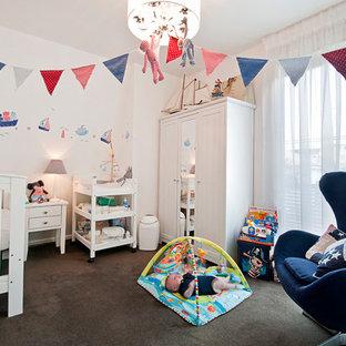 Modelo de habitación de bebé neutra tradicional, grande, con paredes blancas, moqueta y suelo marrón