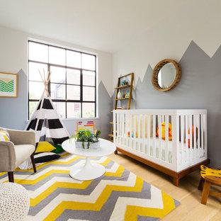 Exemple d'une petit chambre de bébé neutre tendance avec un mur gris, un sol en bois clair et un sol beige.