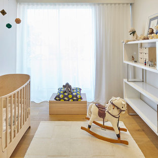 Photo of a contemporary gender-neutral nursery in Sydney with white walls and medium hardwood floors.