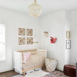 Immagine di una cameretta per neonata stile americano di medie dimensioni con pareti bianche, pavimento in legno massello medio e pavimento marrone