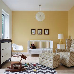 Ejemplo de habitación de bebé neutra contemporánea con paredes amarillas, suelo de madera clara y suelo beige
