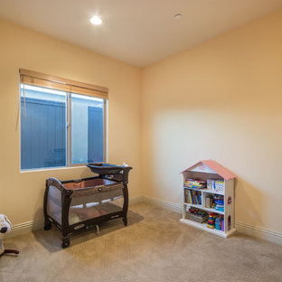 Small mediterranean gender neutral nursery in Los Angeles with beige walls and carpet.