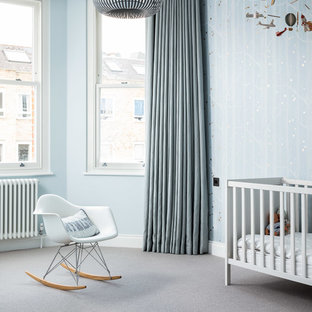 Inspiration for a contemporary nursery for boys in London with blue walls, carpet and grey floors.