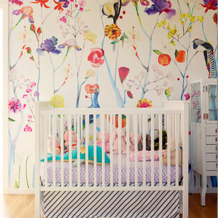 Photo of a small contemporary nursery for girls in Seattle with multi-coloured walls and medium hardwood floors.