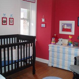 Immagine di una cameretta per neonati neutra minimal con pareti rosse e pavimento in legno massello medio