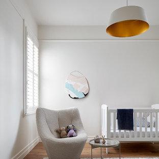 Modern gender-neutral nursery in Melbourne with white walls, medium hardwood floors and brown floor.