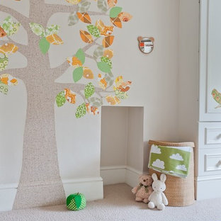 This is an example of a small eclectic gender neutral nursery in London with beige walls, carpet and beige floors.