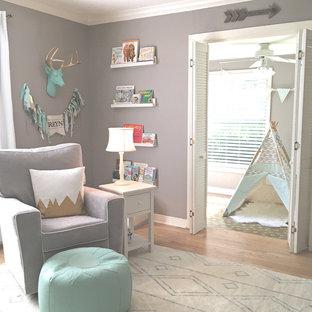 Großes Klassisches Babyzimmer mit grauer Wandfarbe und hellem Holzboden in Austin