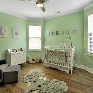 Foto di una grande cameretta per neonato tradizionale con pareti verdi, parquet scuro e pavimento marrone