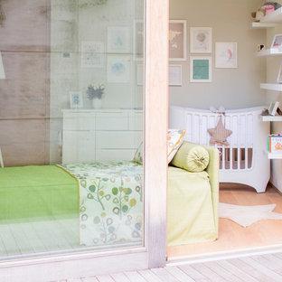 Ejemplo de habitación de bebé neutra actual, pequeña, con paredes blancas y suelo de madera clara
