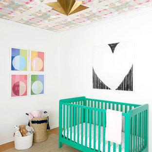 This is an example of a contemporary nursery for girls in Los Angeles with white walls, medium hardwood floors and brown floor.