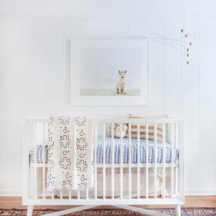 Ejemplo de habitación de bebé neutra contemporánea con paredes blancas