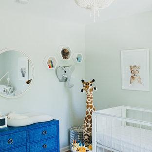 Modelo de habitación de bebé neutra contemporánea con paredes verdes, suelo de madera en tonos medios y suelo marrón