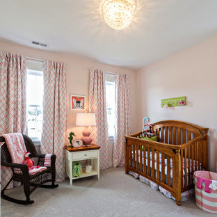 Mid-sized farmhouse girl carpeted nursery photo in Other with pink walls