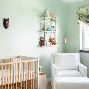 Imagen de habitación de bebé neutra actual con paredes verdes, suelo de madera en tonos medios y suelo marrón