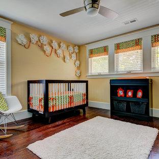 Modern inredning av ett mellanstort könsneutralt babyrum, med orange väggar och mörkt trägolv