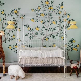 Ejemplo de habitación de bebé neutra contemporánea, grande, con paredes verdes, suelo de madera oscura y suelo marrón
