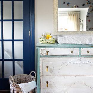 Esempio di una cameretta per neonati neutra shabby-chic style con pareti bianche e parquet scuro