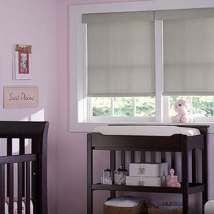 Immagine di una cameretta per neonata classica di medie dimensioni con pareti rosa