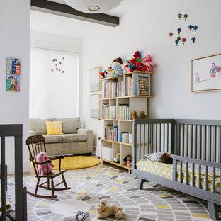 Modelo de habitación de bebé neutra actual, de tamaño medio, con paredes blancas, moqueta y suelo multicolor