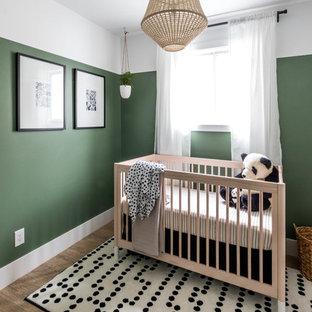 Diseño de habitación de bebé neutra minimalista, pequeña, con paredes verdes, suelo vinílico y suelo marrón