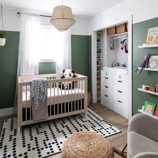 Exemple d'une petit chambre de bébé neutre moderne avec un mur vert, un sol en vinyl et un sol marron.