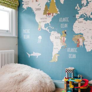 Ejemplo de habitación de bebé niño actual, pequeña, con paredes azules, suelo de madera clara y suelo marrón