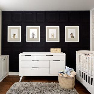 Diseño de habitación de bebé neutra clásica renovada, de tamaño medio, con paredes negras y suelo de madera oscura