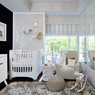 Foto de habitación de bebé neutra moderna, de tamaño medio, con paredes negras y suelo de madera oscura