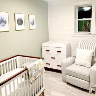 Esempio di una piccola cameretta per neonati neutra minimal con pareti verdi, pavimento in laminato e pavimento grigio