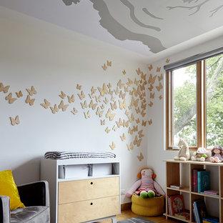 Esempio di una cameretta per neonata minimal con pareti bianche, parquet chiaro e pavimento marrone
