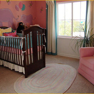 Esempio di una cameretta per neonata design di medie dimensioni con pareti rosa e moquette