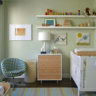 Design ideas for a modern nursery for boys in New York with green walls and dark hardwood flooring.