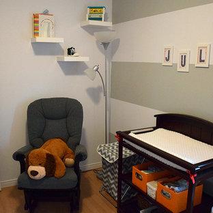 Idee per una piccola cameretta per neonato minimalista con pareti grigie e pavimento in compensato