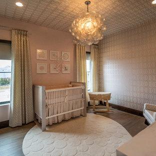 Immagine di una grande cameretta per neonata design con pareti rosa, pavimento in gres porcellanato e pavimento marrone