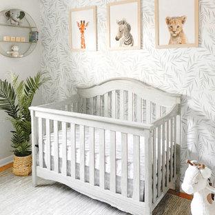 Foto de habitación de bebé neutra tradicional, de tamaño medio, con paredes beige, suelo de madera en tonos medios y suelo marrón
