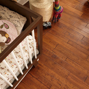 Design ideas for a shabby-chic style nursery in Raleigh with blue walls, medium hardwood floors and brown floor.