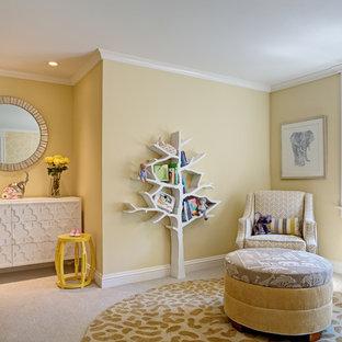 Immagine di una grande cameretta per neonati neutra tradizionale con pareti gialle e moquette