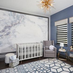 Réalisation d'une chambre de bébé garçon tradition de taille moyenne avec un mur bleu et un sol en bois clair.