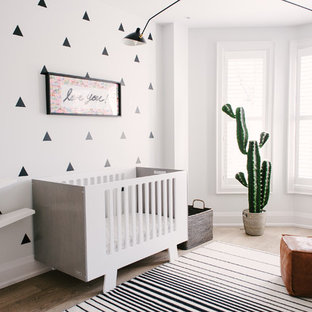 Mid-sized contemporary gender-neutral nursery in Toronto with grey walls, light hardwood floors and brown floor.