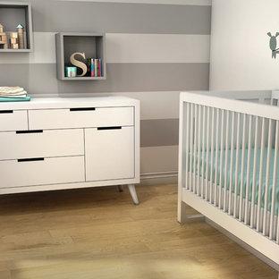 Minimalistisk inredning av ett babyrum, med plywoodgolv och flerfärgade väggar