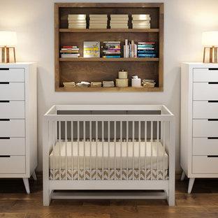 Foto på ett minimalistiskt babyrum, med beige väggar och plywoodgolv