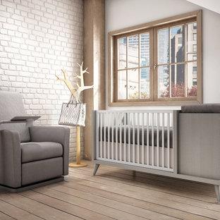 Cette photo montre une chambre de bébé neutre scandinave avec un mur beige et un sol en contreplaqué.