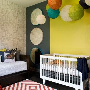 Cette photo montre une chambre de bébé neutre tendance de taille moyenne avec un mur multicolore et un sol en bois foncé.